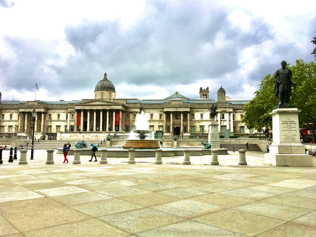 Trafalgar Square on a cloudy day with fountains and the National Gallery in the background